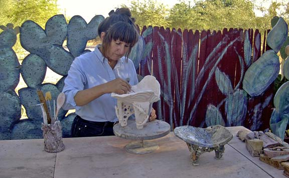 Scrap plywood cut into prickly pear shapes and painted extend a split rail fence.